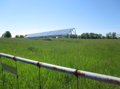Farm entrance with solar panel array in foreground