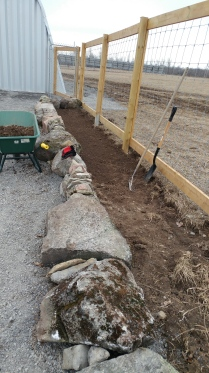 Raised garden beds using the many rocks that dot our farm